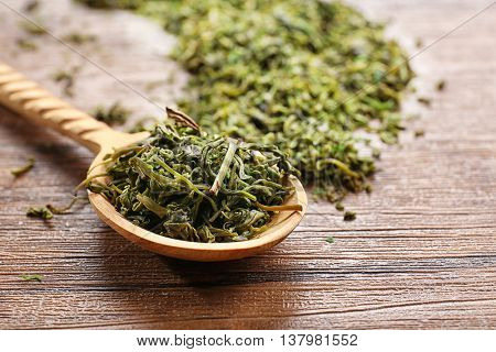 Dry tea leaves in wooden spoon on table