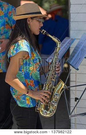 ROMANIA TIMISOARA - JULY 7 2016: Young singer girl at saxophone from Costa Rica present at the folk festival