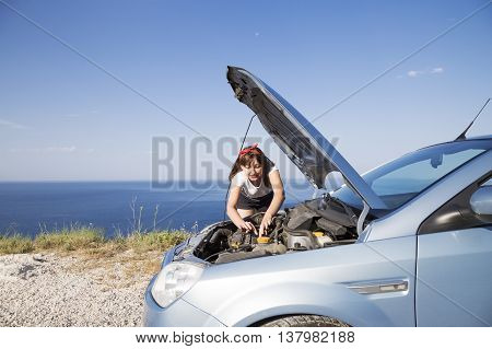 A woman repair the car her car broke down on the road side.