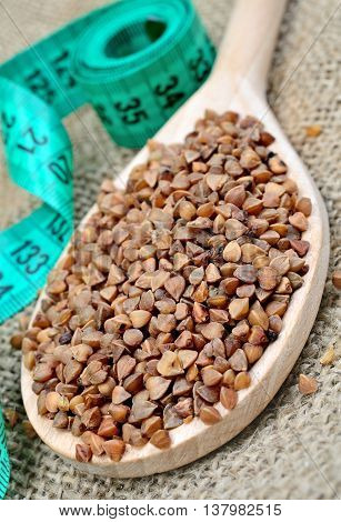 Spoon with buckwheat seeds and centimeter on rustic table