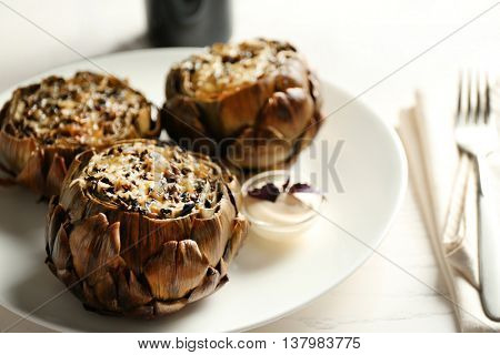 Baked artichokes with cheese on white plate
