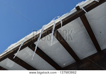 Icicle hanging under the roof of house.