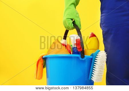 Hand holding plastic bucket with brushes, gloves and detergents on yellow background