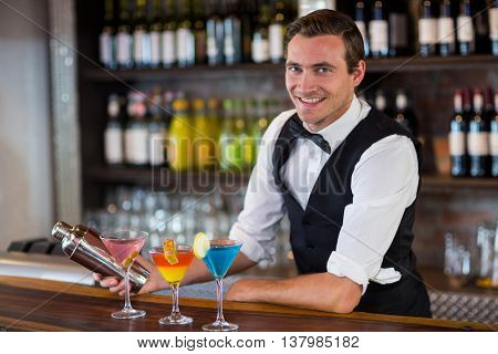 Portrait of bartender mixing a cocktail drink in cocktail shaker at bar