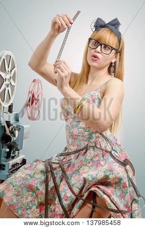 sexy pin-up girl with a film reel and cinema projector