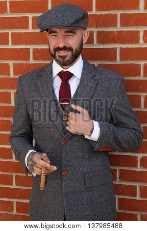 A groom in his suit smoking a cigar on his wedding day