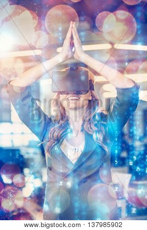 Happy businesswoman with hands joined using virtual reality simulator in office