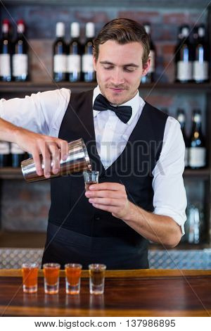 Bartender pouring tequila into shot glasses at bar counter in bar