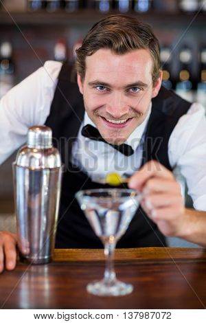 Portrait of bartender garnishing cocktail with olive on bar counter in bar