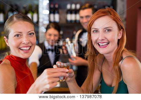 Portrait of happy friends holding a tequila shot in front of bar counter in bar
