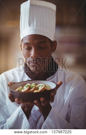 Close-up of chef with eyes closed smelling food in the kitchen