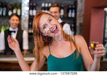 Portrait of drunk woman with tequila shot laughing in front of counter in bar
