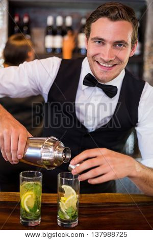 Portrait of bartender pouring a drink from a shaker to a glass on bar counter in bar