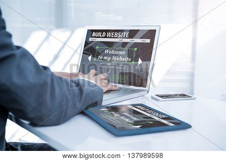 Composite image of build website interface against businessman using his computer