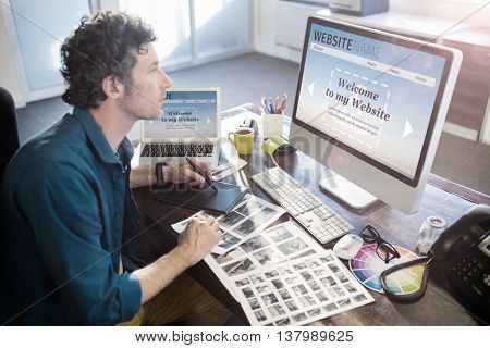 Composite image of build website interface against photographer working on his computer