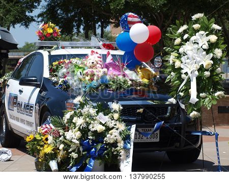 Dallas,USA,08July2016. In the afterman of Thursdays shootings, memorials are placed in from the the Jack Evans Police Headquarters in Dallas. There are two cars. One Dallas Police and one, Dallas Area Rapid Transit (DART).in Dallas, on Thursday,July 7, 20