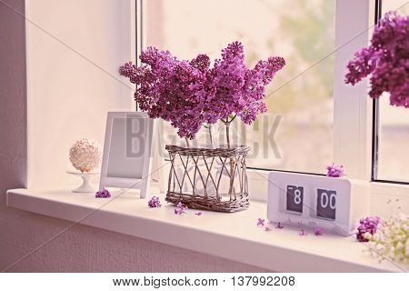 Lilac bouquet in glass jar on windowsill