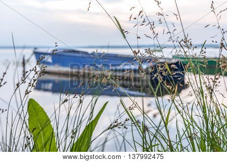 The blue boat and the lake on a background not in focus and a grass ashore.