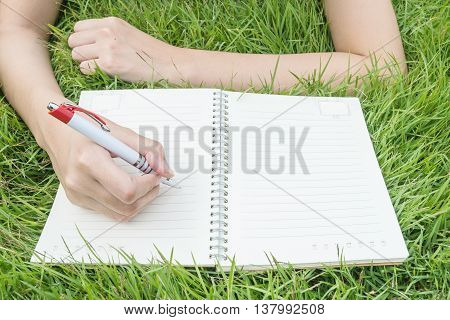 Closeup asian woman lying on grass field textured background for writing on note book under day light in the garden