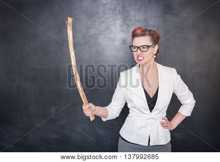 Angry Screaming Teacher With Wooden Stick On Blackboard Background