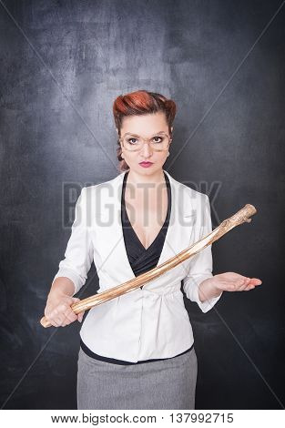 Strict Teacher With Wooden Stick On Blackboard Background
