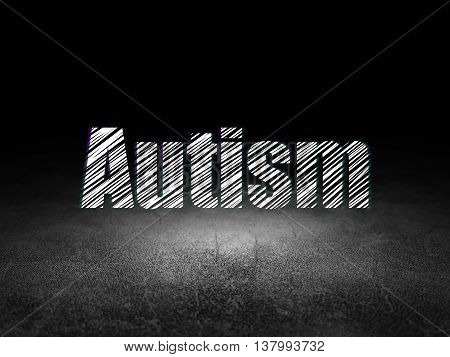 Healthcare concept: Glowing text Autism in grunge dark room with Dirty Floor, black background