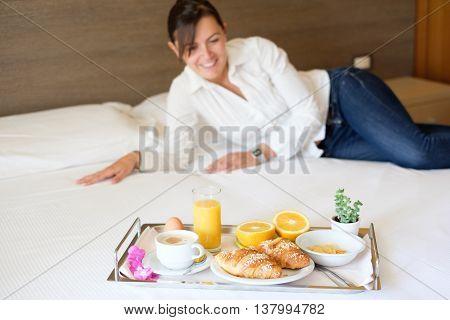 Woman having breakfast in her hotel room main focus on the breakfast tray