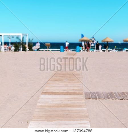 wooden boardwalk at La Malvarrosa Beach in Valencia, Spain, with the Mediterranean sea and unrecognizable sunbathers in the background