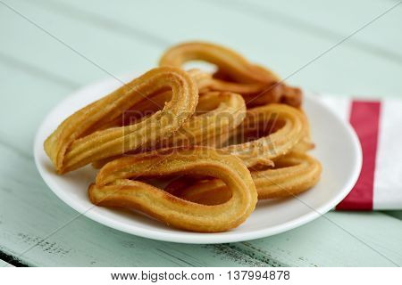 closeup of some churros typical of Spain on a white ceramic plate, placed on a pale blue rustic wooden table