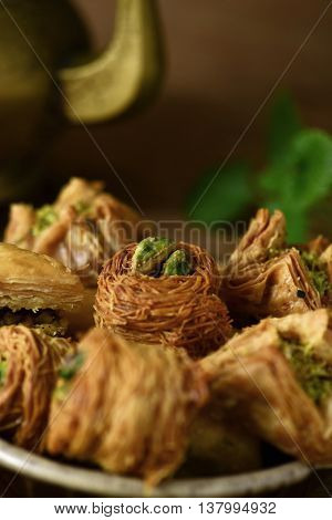 closeup of an assortment of different baklava pastries in an earthenware bowl on a table and a golden teapot in the background