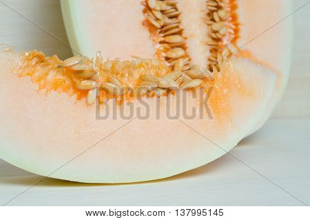 Melon or cantaloupe sliced on wooden board with seeds (Also called as cantelope cantaloup muskmelon mushmelon rockmelon sweet melon Persian melon spanspek)