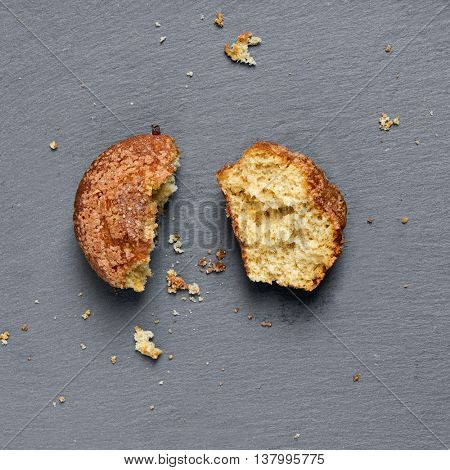 high-angle shot of a plain muffin broken in two pieces on a slate background