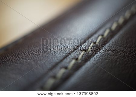 Macro detail of a white thread stitching black and brown stitched leather wallet