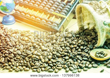 Coffee beans from a bag and abacus on the wooden.