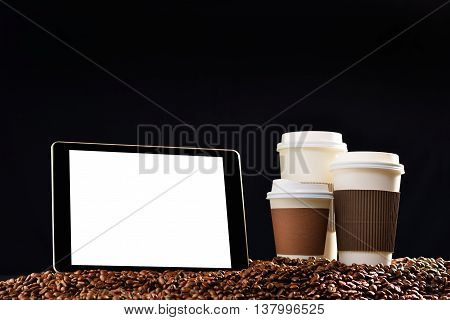 Tablet computer with blank white screen and paper cups of coffee on pile of coffee beans