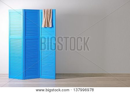 Blue folding screen with towel in room