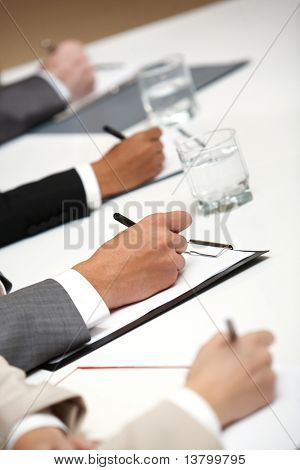 Image of four people's hands writing