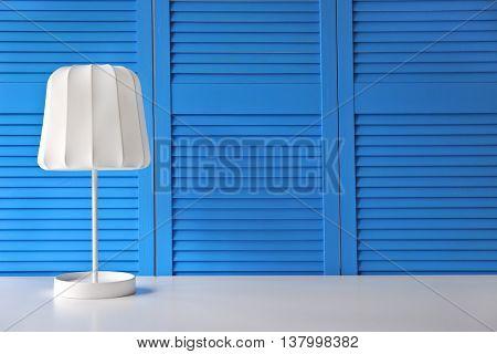Stylish lamp on blue folding screen background