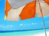 picture of summer beach  - A brightly colored beach umbrella contrasts against a azure blue ocean and sky - JPG