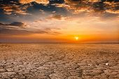 Global worming concept - cracked scorched earth soil drought desert landscape dramatic sunset poster