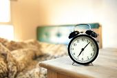Постер, плакат: Black Retro Alarm Clock And Bed In Morning Light 7 00 Am Alarm Clock In Morning Shallow Depth Of F