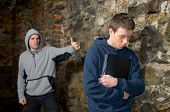 stock photo of bullying  - Angry bully bullying a young sad boy looking down near a rock wall - JPG