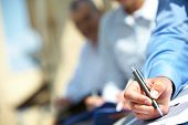 stock photo of summary  - Male hand over paper making notes at seminar - JPG