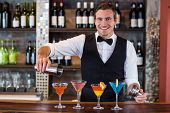 Portrait of bartender pouring a orange martini drink in the glass at bar poster