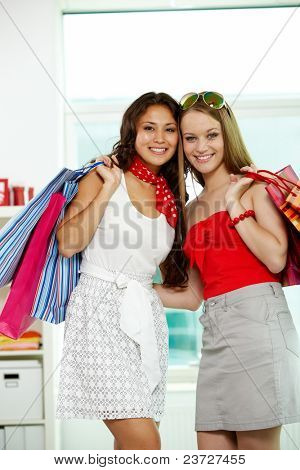 Retrato de duas meninas maravilhosas com paperbags olhando para câmera