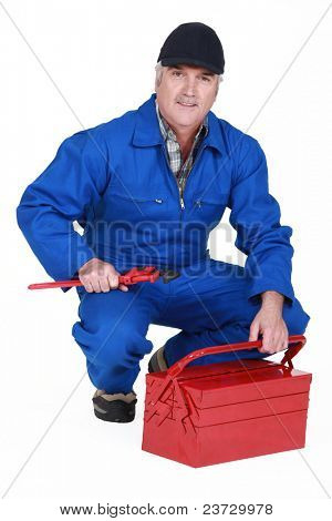 senior craftsman holding a spanner and a tool box