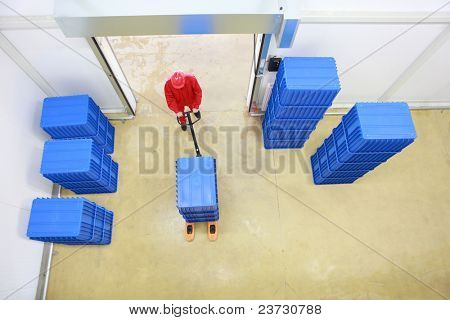 overhead view of worker in red uniform loading blue containers to storehouse