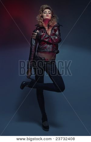picture of fashionable woman in black clothes in red light