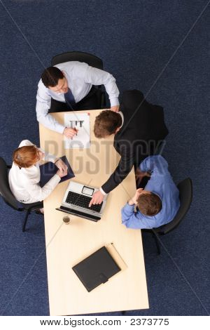 Man Making Presentation On Laptop At Small Group Meeting