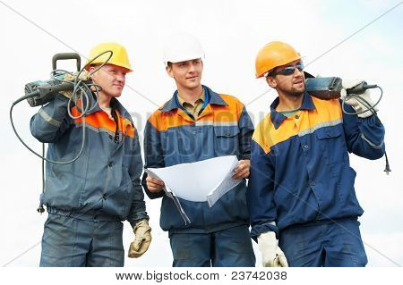 positive Builder worker with pneumatic hammer drill equipment over blue sky